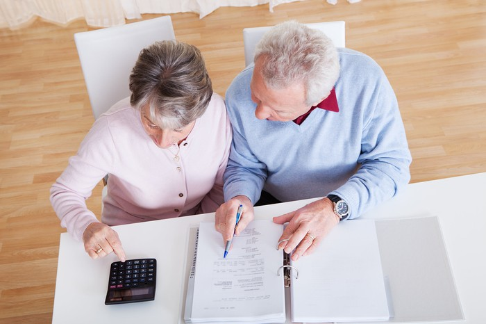 Overhead shot of older couple reviewing papers at desk with calculator