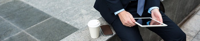 A seated man in a suit, holding a tablet, with a smartphone and a cup of coffee next to him.