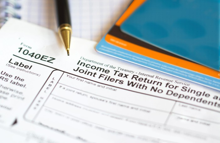 A 1040EZ tax form, with a pen and other items.