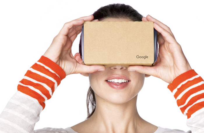 Woman holding a Google Cardboard device to her face.