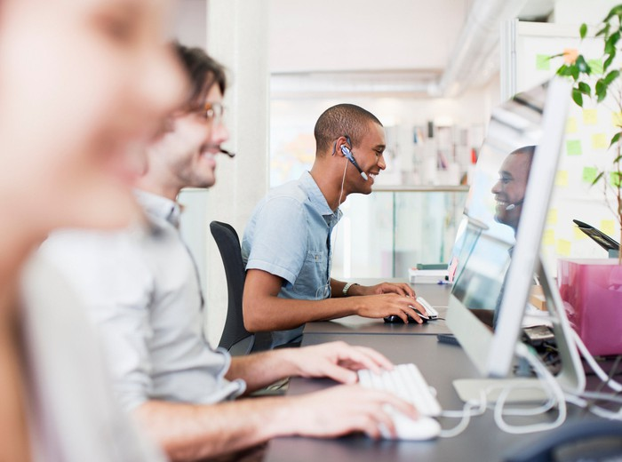 Call center employees wearing headsets.