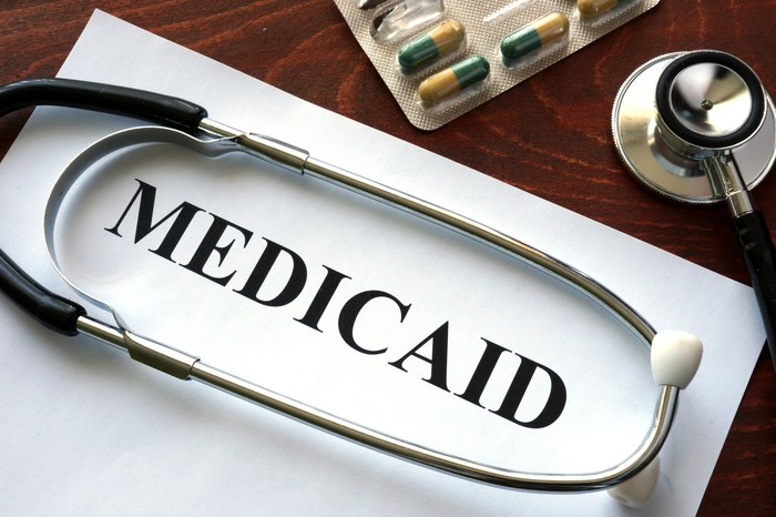 A stethoscope sitting on a card that says Medicaid, along with some prescription pills.