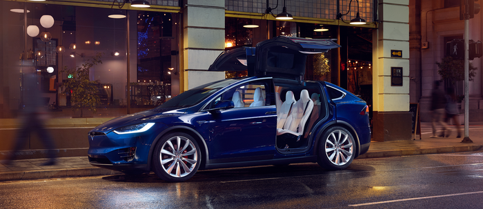 Model X on a street with open Falcon Wing Doors