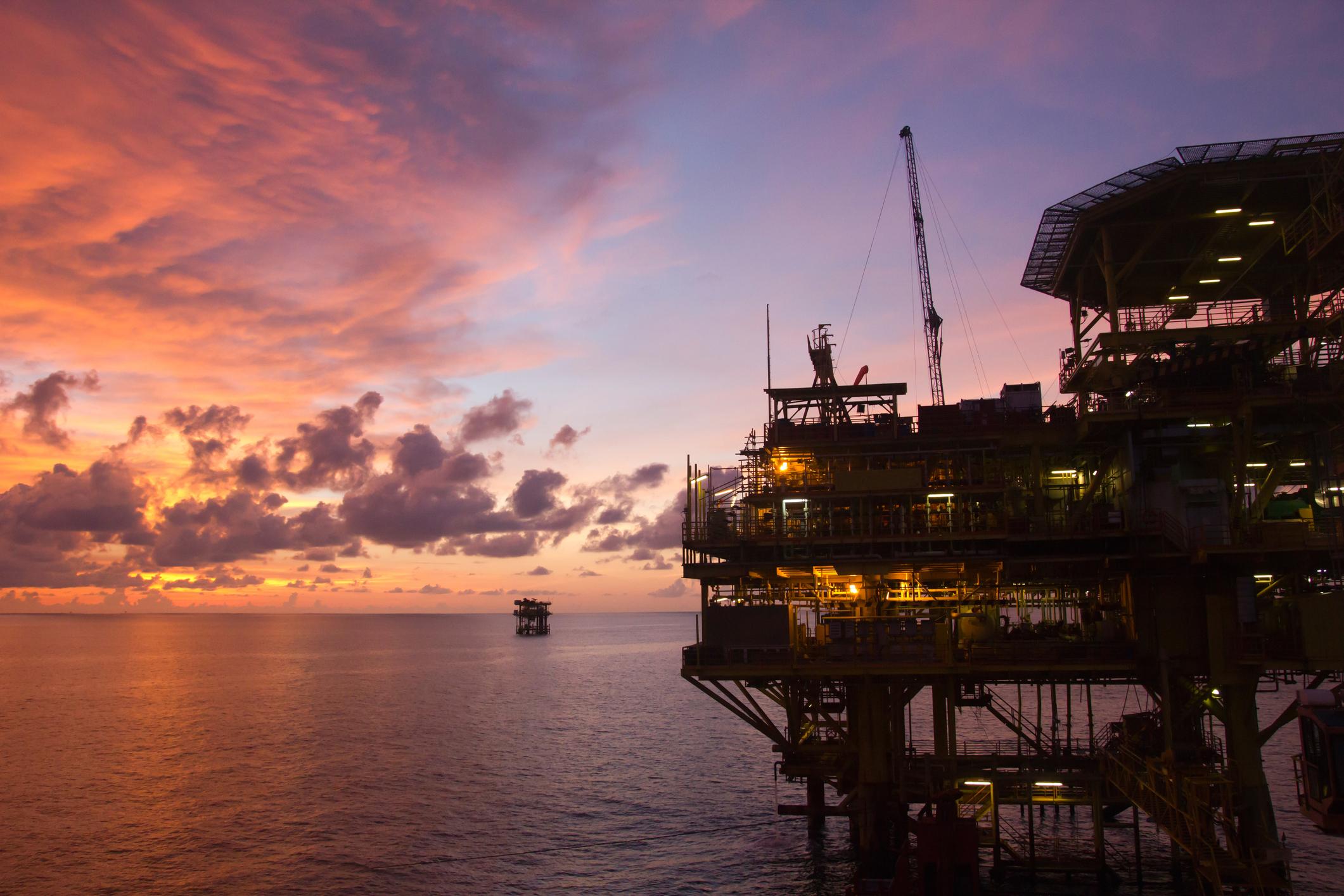 Oil production platform at sunset