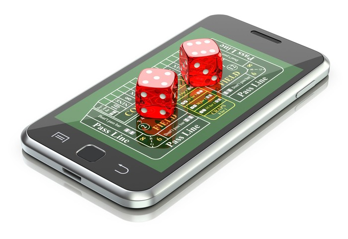 Dice on top of a smartphone showing a gambling app.