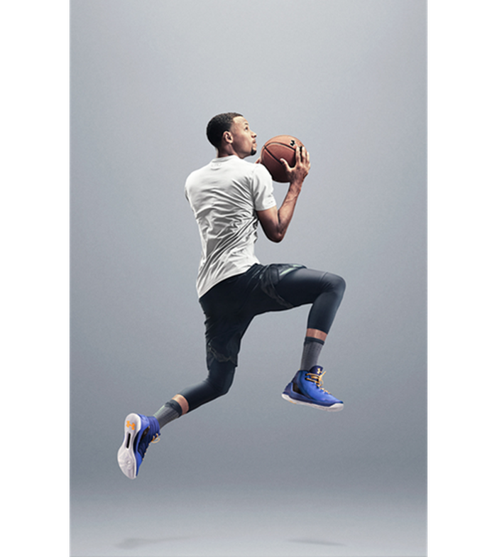 Steph Curry in casual-looking but athletic clothing jumping with a basketball.