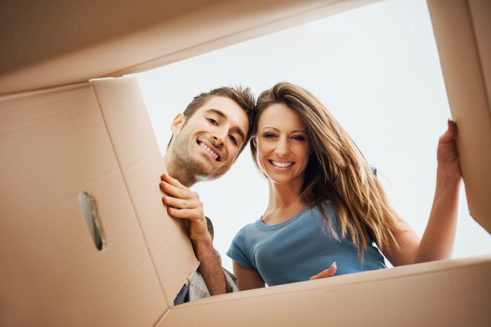 A man and woman peer happily into a cardboard package delivery.