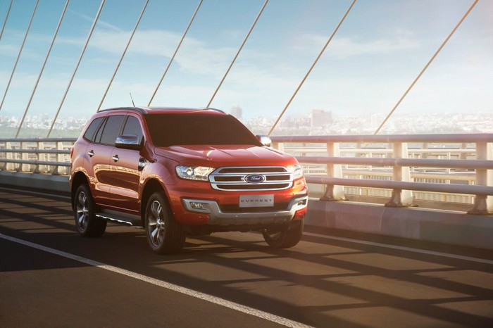 A red Ford Everest driving on a bridge.