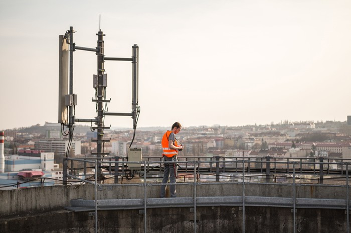 A telecom worker performs a check on a cell tower on top of a building.