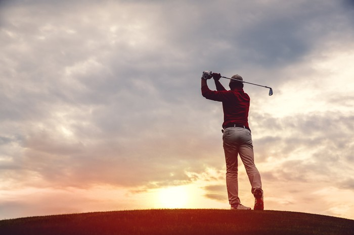 Silhouette of a man golfing at dusk.