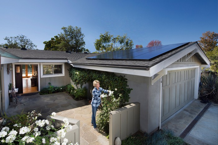 A woman gardening at a house with a residential rooftop solar system.