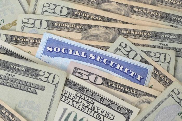 A Social Security card amid a pile of cash.