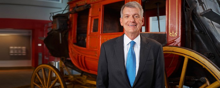 Wells Fargo CEO Tim Sloan in front of a stagecoach.