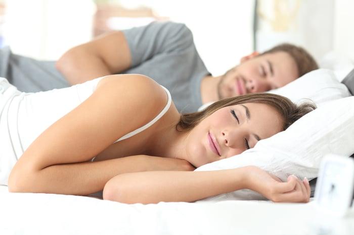Couple sleeping on a mattress.
