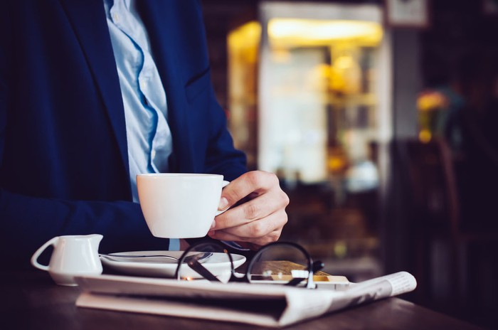 Business man drinking coffee with folded newspaper.