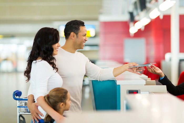 Young happy family handing over tickets at airline counter.