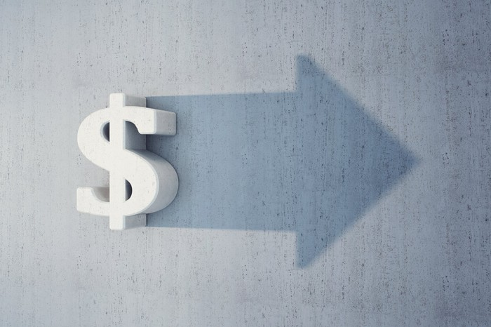 A dollar sign casting a shadow that forms a forward-pointing arrow.