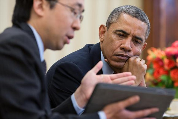 Former President Barack Obama reviewing Obamacare enrollment data on a tablet.