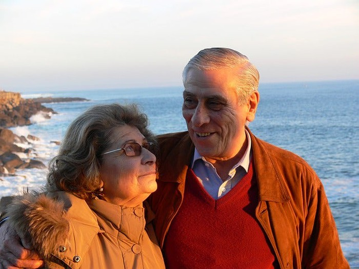 An elderly married couple smiling at one another.