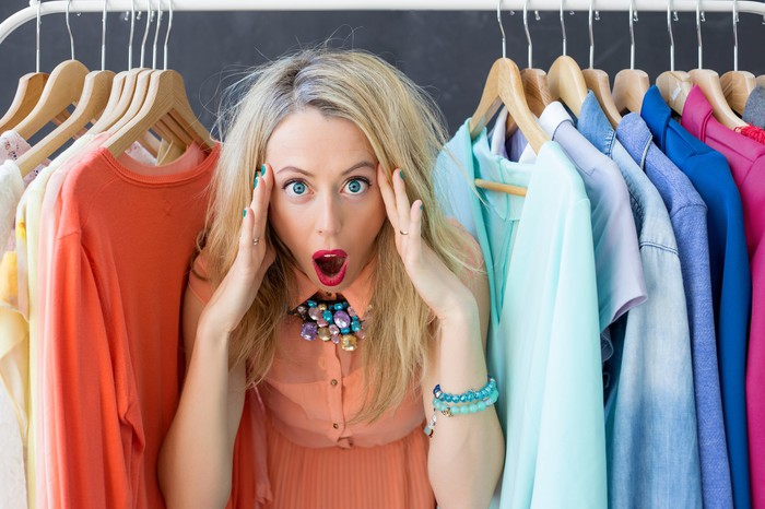 A surprised woman standing in the middle of a row of clothes.