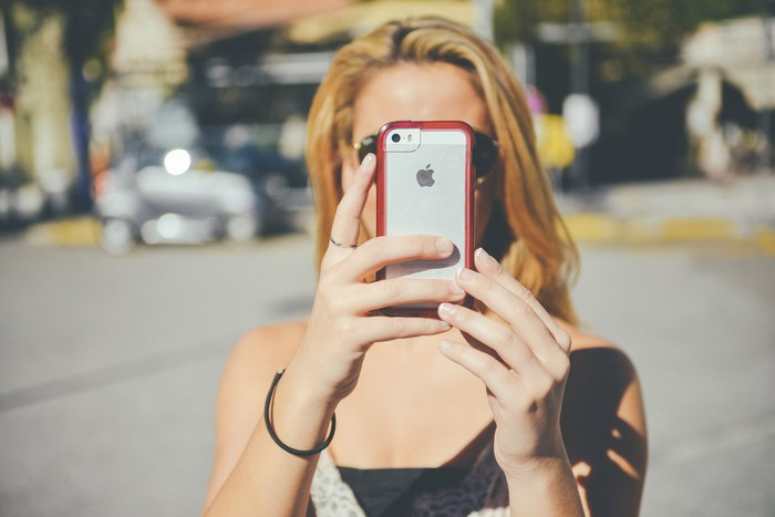 A woman holds up an iPhone to take a selfie.