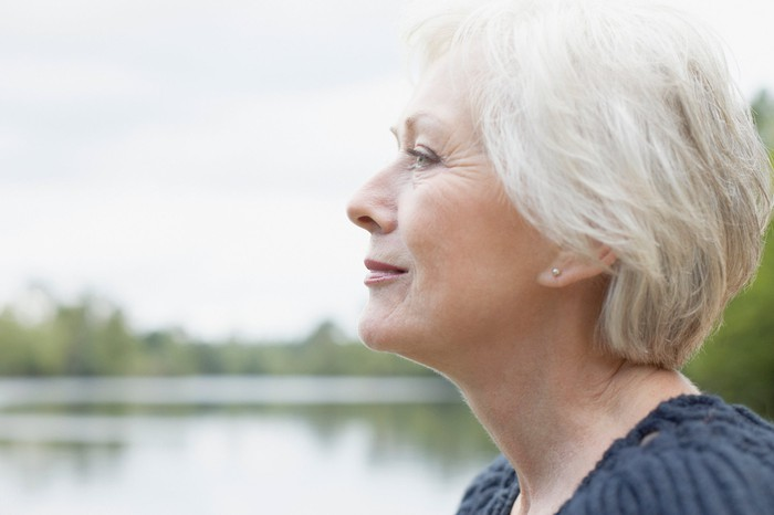 Side profile of an older woman, smiling, as she stands by the water.