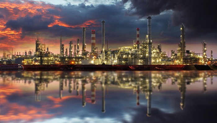 Refinery at sunset, with mirror image reflected in still water