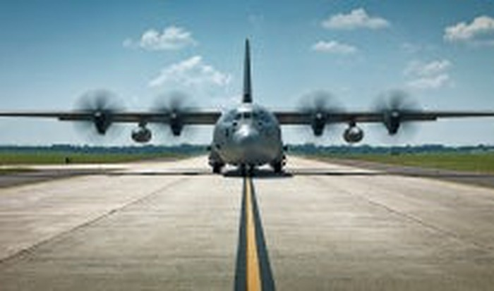 A C-130 airplane on a runway.
