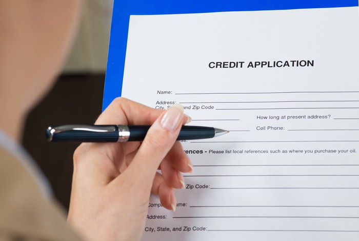 A hand holding a pen fills out a credit application.