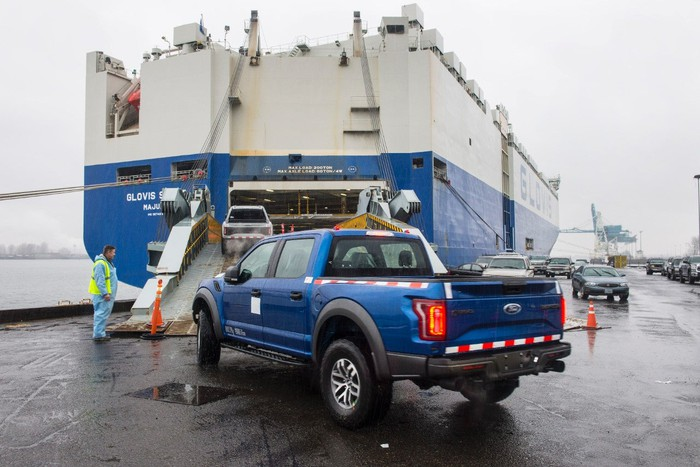 A blue Ford F-150 Raptor being loaded onto a cargo ship.