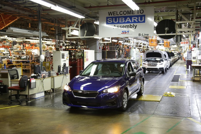 The first 2017 Impreza, a blue sedan, rolls off a factory assembly line.