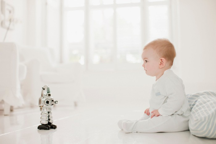 A baby sitting next to a toy robot.