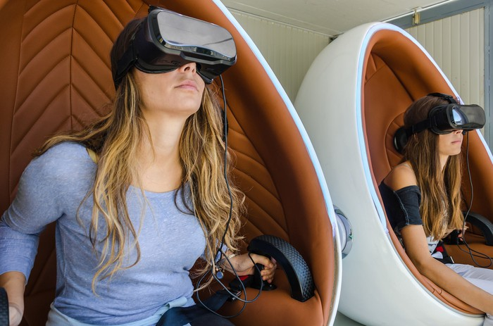 Two women sitting in pods with virtual-reality headsets on.
