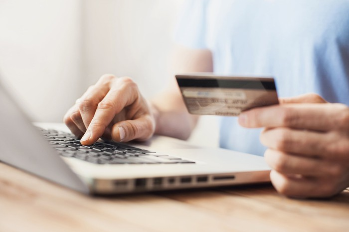 hands shown of someone at laptop with credit card, as if shopping online