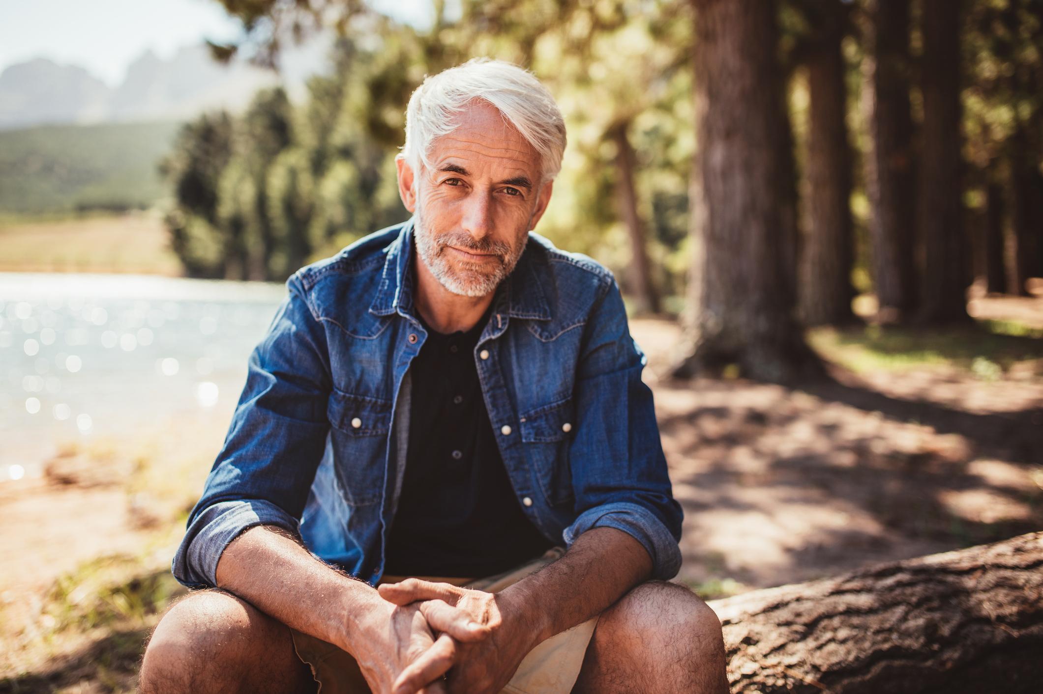An older man sitting in an outdoor scene.