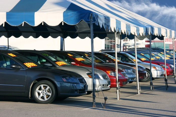 Row of cars under an awning at a dealership.