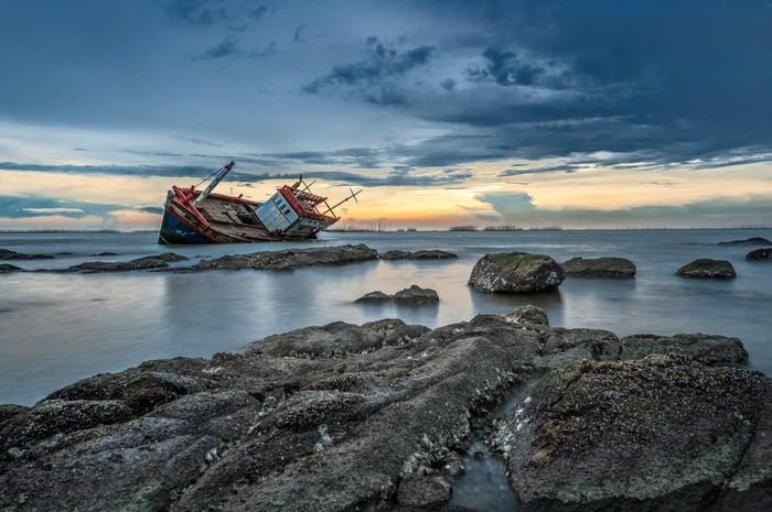 Cargo ship on rocks.