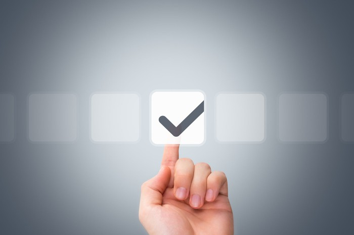 Male hand touching a button and ticking a check box.
