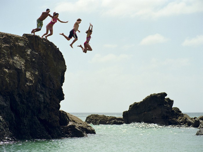 Four people jumping off a short cliff and into water.