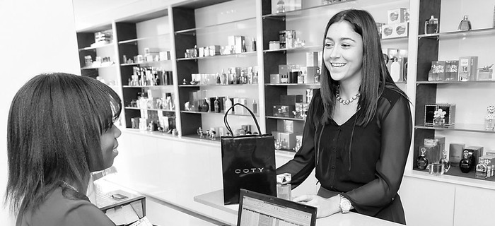 A woman behind a counter hands a makeup bag to another woman in a black and white photo.