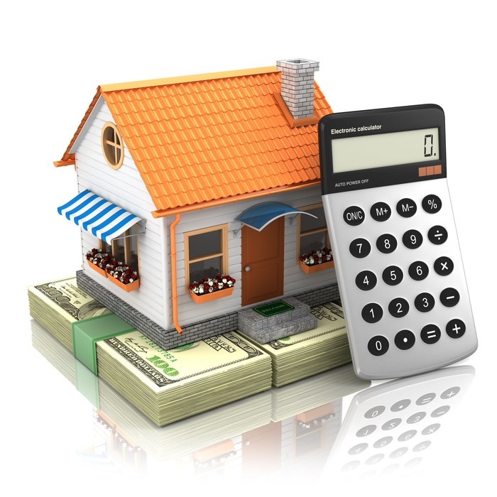 A calculator leans against a tiny house, which is sitting on stacks of money.