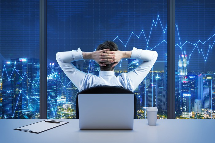 A man sits in an office, back to his desk, hands clasped behind his head, as he looks out the window at a scene of rising stock charts.