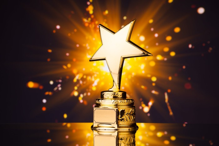 Light shoots out from behind a golden trophy, topped with a star.