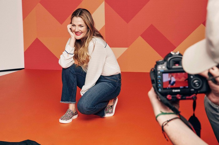 Crocs ambassador Drew Barrymore being photographed wearing a pair of Crocs.