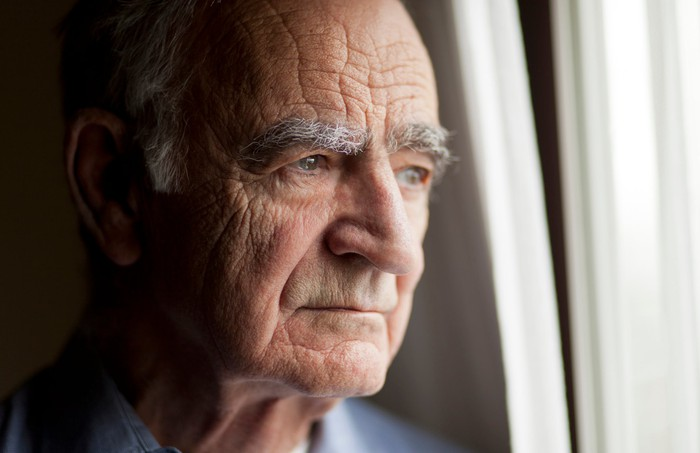 An elderly man stares deeply out a window in his home.