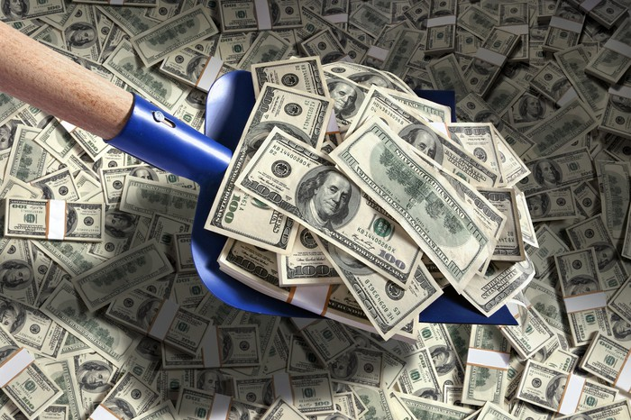 A shovel scooping up piles of cash.