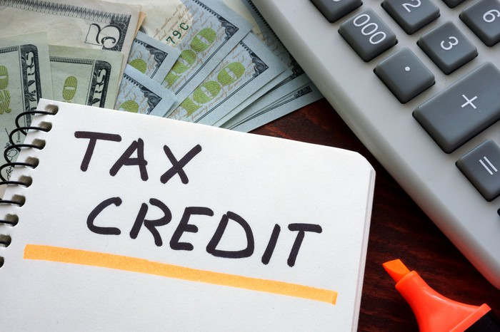 """Words """"tax credit"""" written and underlined, next to calculator, money, and highlighter"""