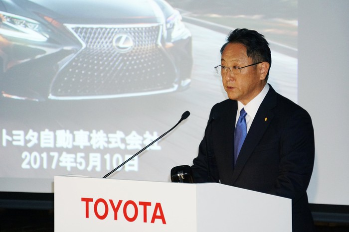 Toyoda is shown speaking at a podium in front of a slide screen.