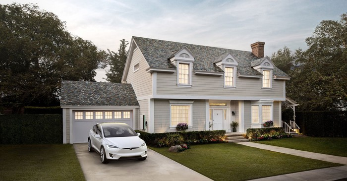 Rendering of home with solar roof and Tesla car in the driveway.