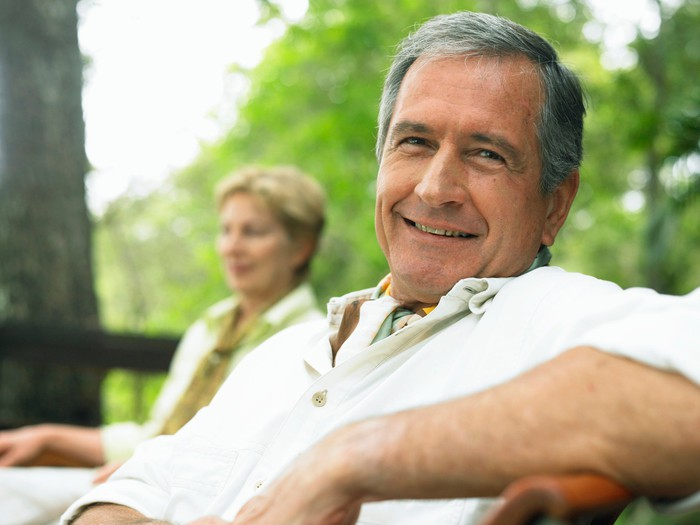 An older couple, smiling and sitting outdoors.